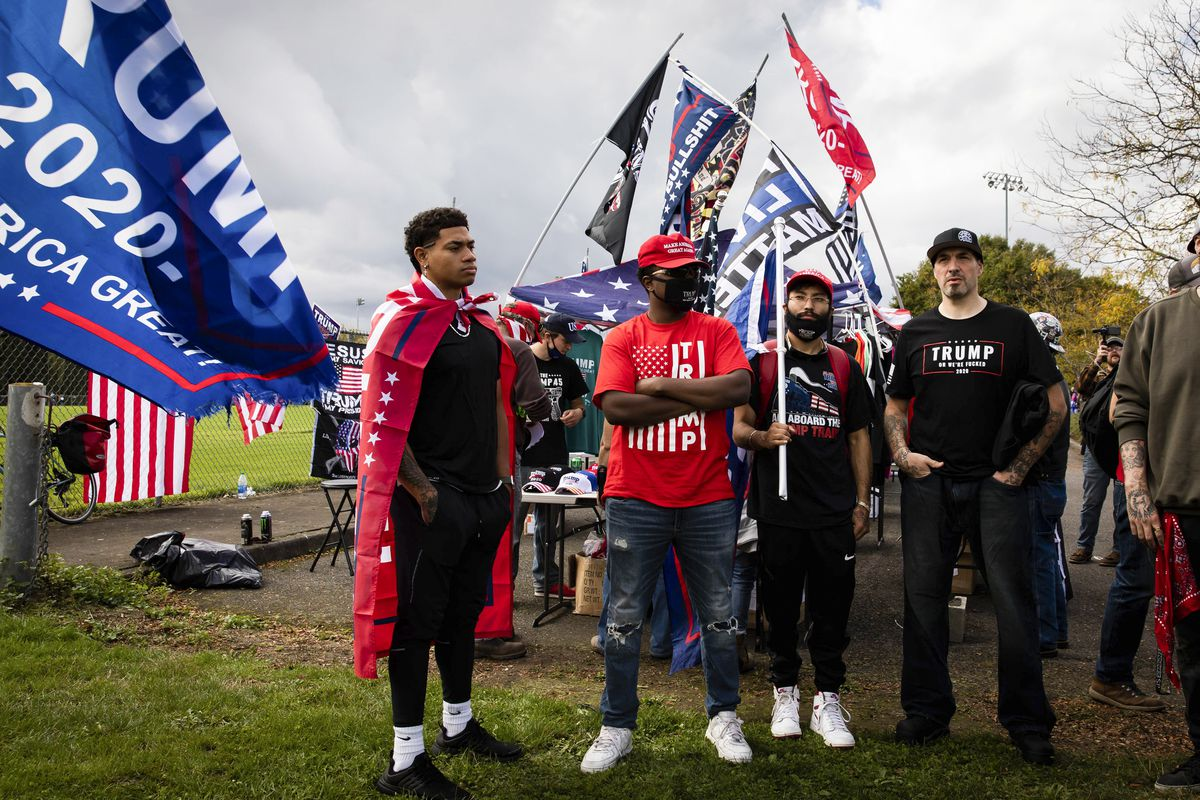 Blue Trump 2020 flags encircle a group of men in a grassy field; the main subjects of the photo are two Black men; one in all black, with a Trump flag tied around his neck, forming a cape; the other with a red American flag shirt on and a MAGA hat.
