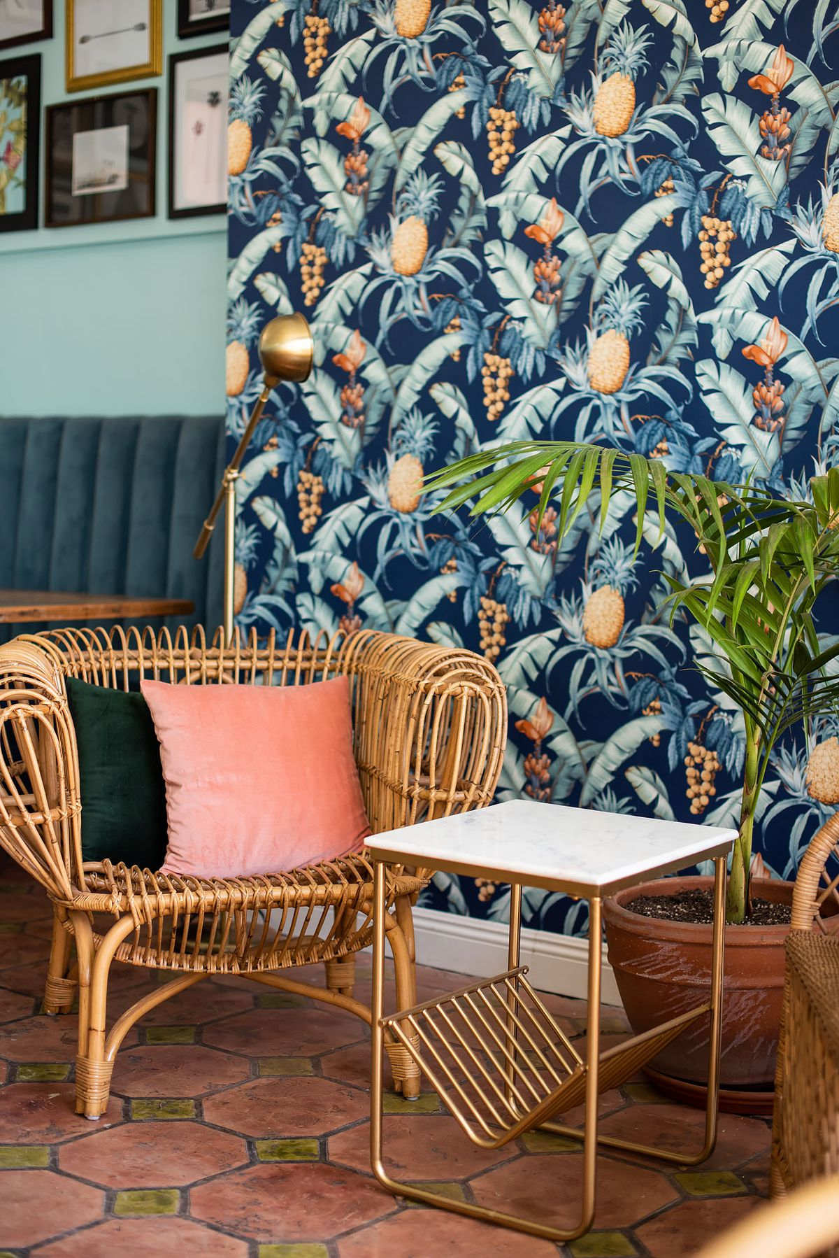 A rattan chair in front of a colorful bar wallpaper.