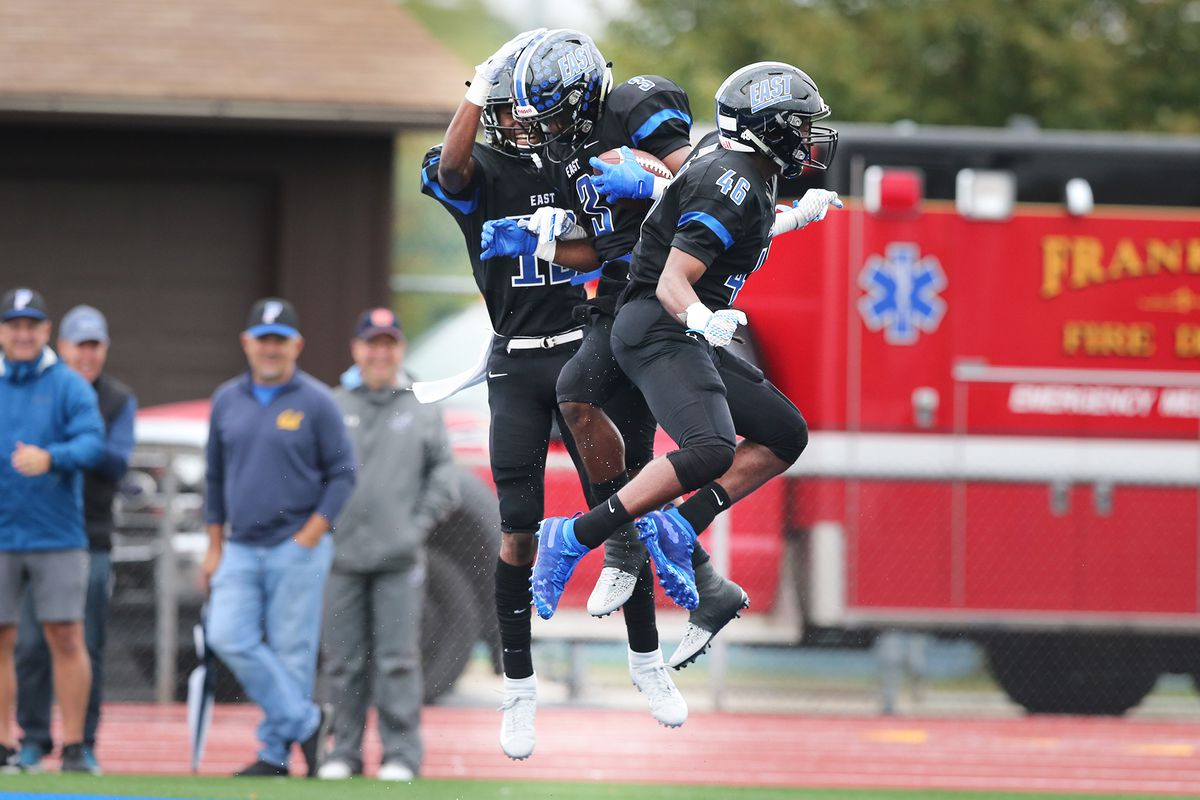 Lincoln-Way East's Mason Pierre-Antoine (13) and Sevren Stuckey (46) celebrate with A.J. Henning (3) after he scored one of his touchdowns against Homewood-Flossmoor.