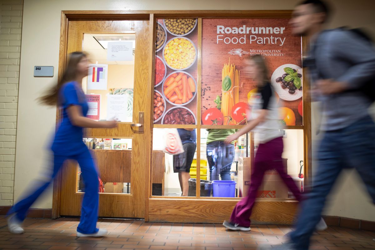 Blurred students walk past a Metropolitan State University of Denver door with a colorful sign that reads: Roadrunner Food Pantry.