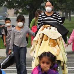 Maricela Pena, center, pushes a relative's baby in a carriage while picking up four of her children at Lewis and Clark Elementary School in Wenatchee, Wash., Thursday, Sept. 20, 2012. Many were wearing masks and covering their faces as the city continues to be chocked with smoke from nearby wildfires. At left, teacher Lucy Garcia wears a mask while on crossing guard duty. Garcia said the masks have been donated to the school and she's been wearing hers when outside since Monday.