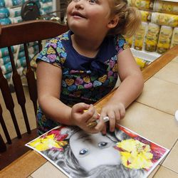 """In this photo taken Monday, Sept. 10, 2012, seven-year-old beauty pageant regular and reality show star Alana """"Honey Boo Boo"""" Thompson signs a photo in her home in McIntyre, Ga. The reality show """"Here Comes Honey Boo Boo"""" centers around Alana, her mother June Shannon and their family."""