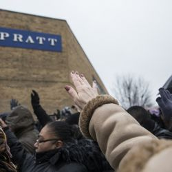 Mourners extend their hands in prayer at a vigil for the five people killed two days earlier in a mass shooting at the Henry Pratt Company in Aurora, Sunday afternoon, Feb. 17, 2019.   Ashlee Rezin/Sun-Times