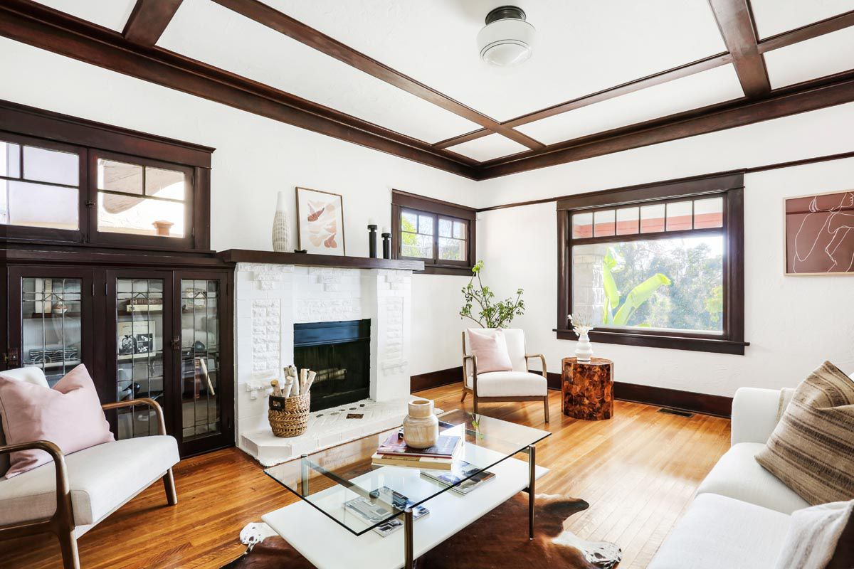 A living room with extensive woodwork and a brick fireplace that has been painted white. The room is furnished with a cowhide rug, glass coffee table, and white sofa.