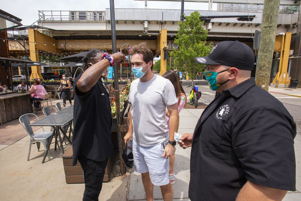 A bouncer with mask outside a bar taking temps of two masked customers.