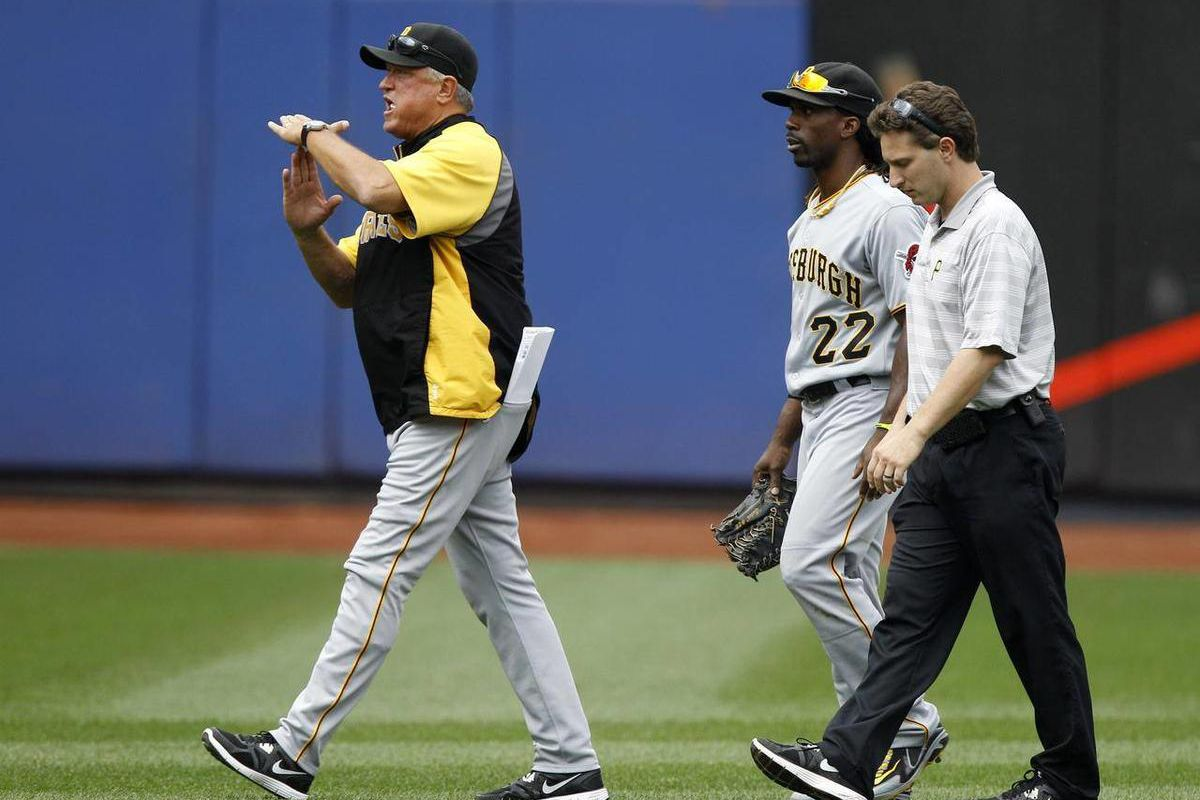 Pittsburgh Pirates manager Clint Hurdle signals to the dugout as he and a trainer leave the field with  Pirates center fielder Andrew McCutchen during their baseball game against the New York Mets at Citi Field in New York, Thursday, Sept. 27, 2012.