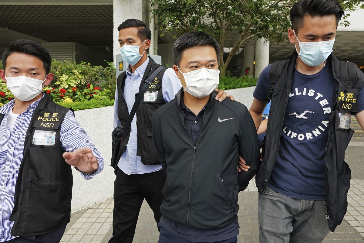 Ryan Law, second from right, Apple Daily's chief editor, is arrested by police officers in Hong Kong Thursday, June 17, 2021.