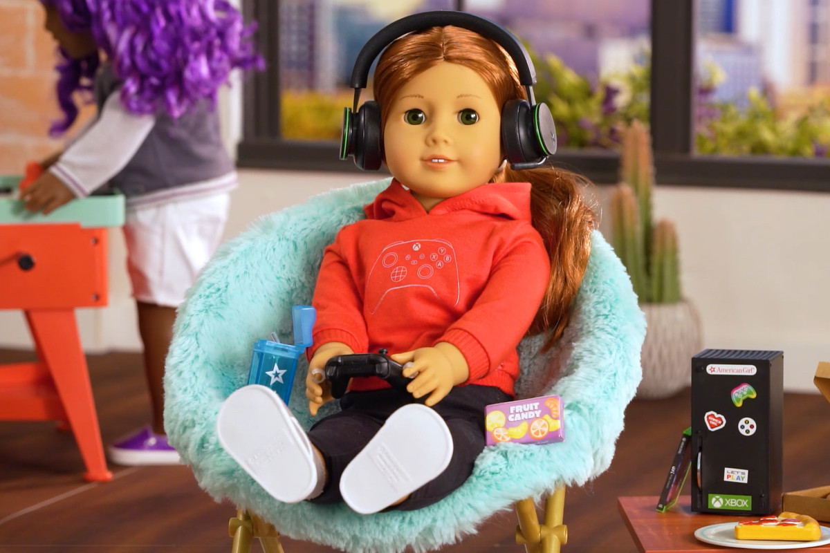 an american girl doll in a cool chair holding a controller