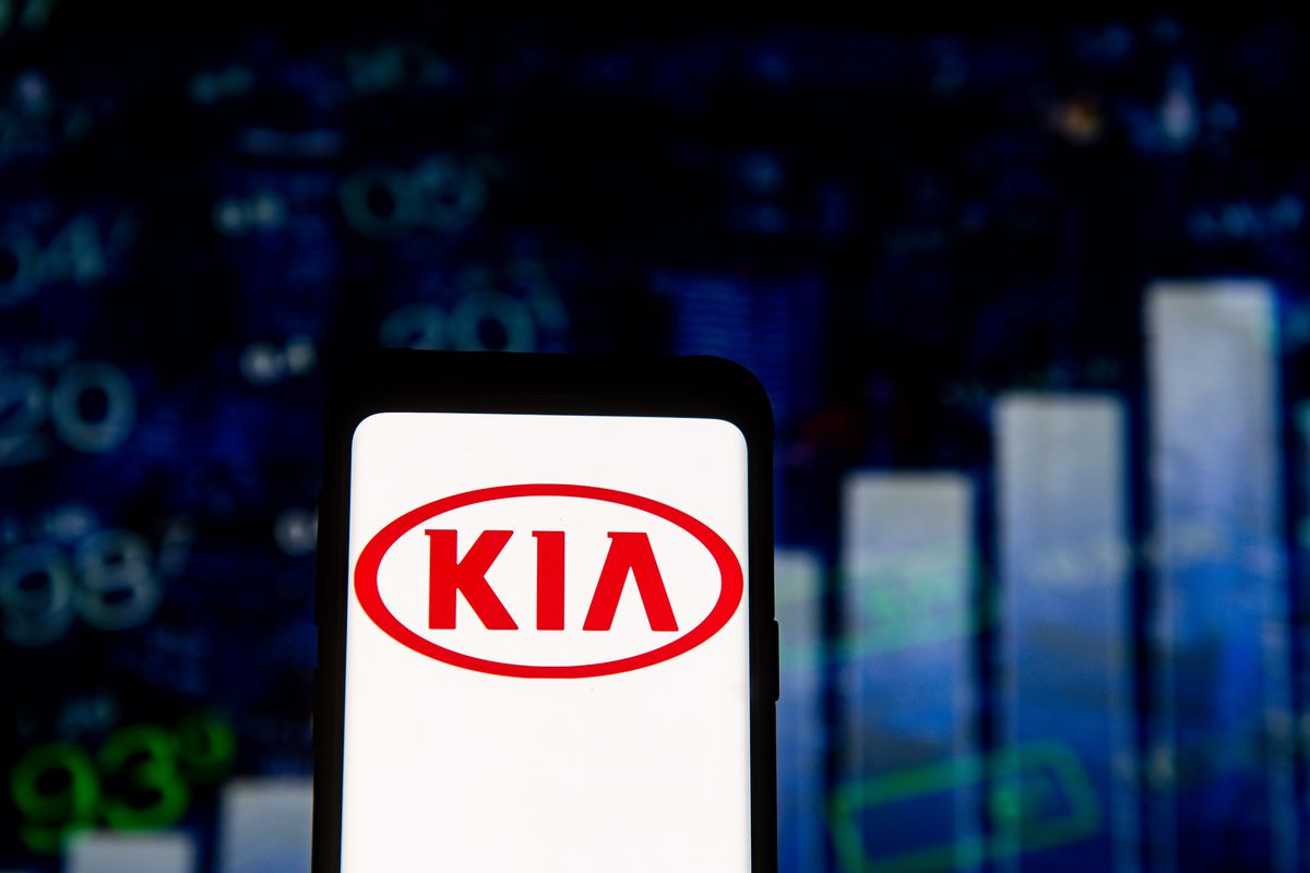 In this photo illustration a KIA logo seen displayed on a...