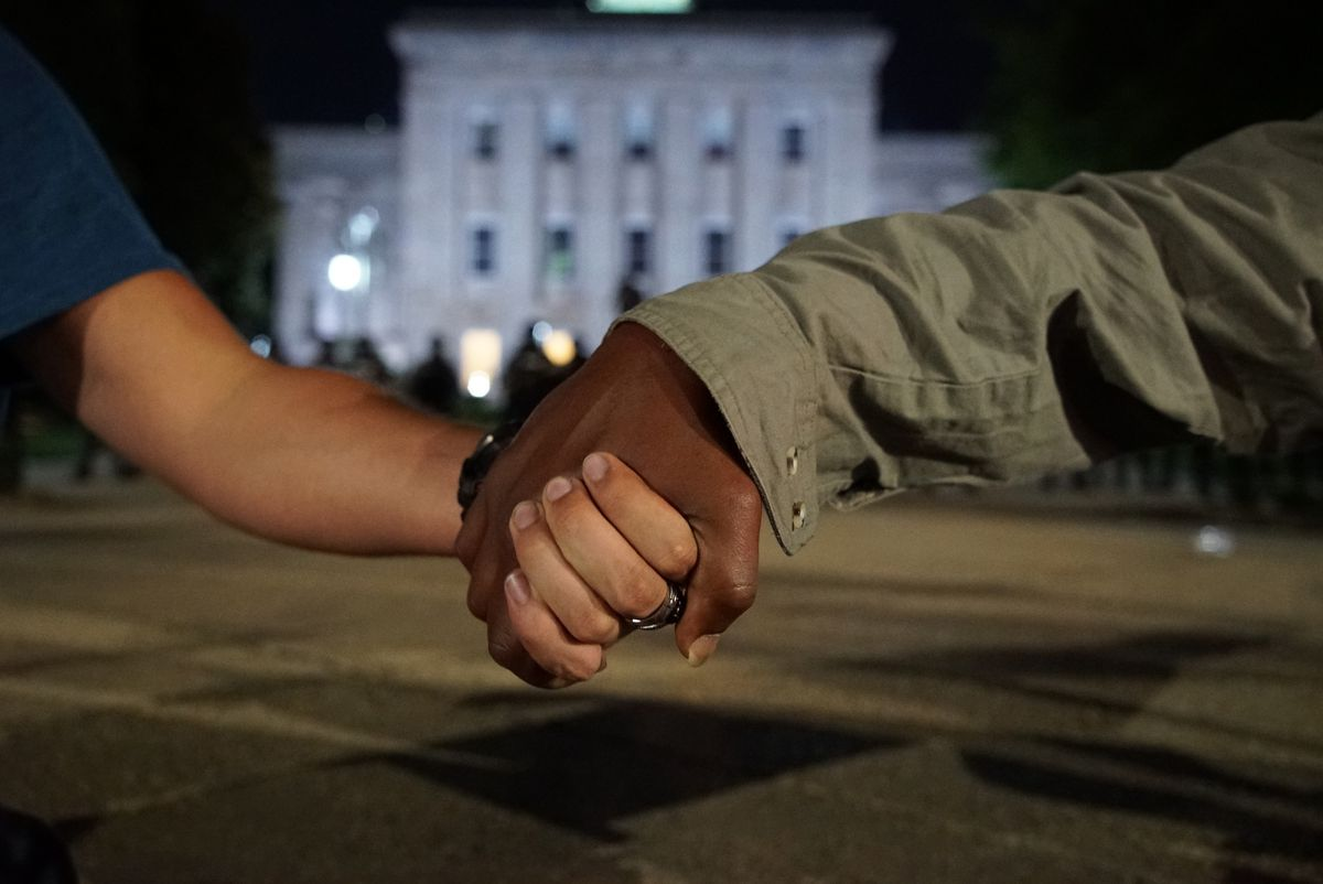 A white man and a black man clasp hands as police in the background guard the old state capitol in Raleigh, N.C., on Monday, June 1, 2020. It was the second day of protests in the North Carolina capital following the death of Minnesotan George Floyd while in police custody. (AP Photo/Allen G. Breed)