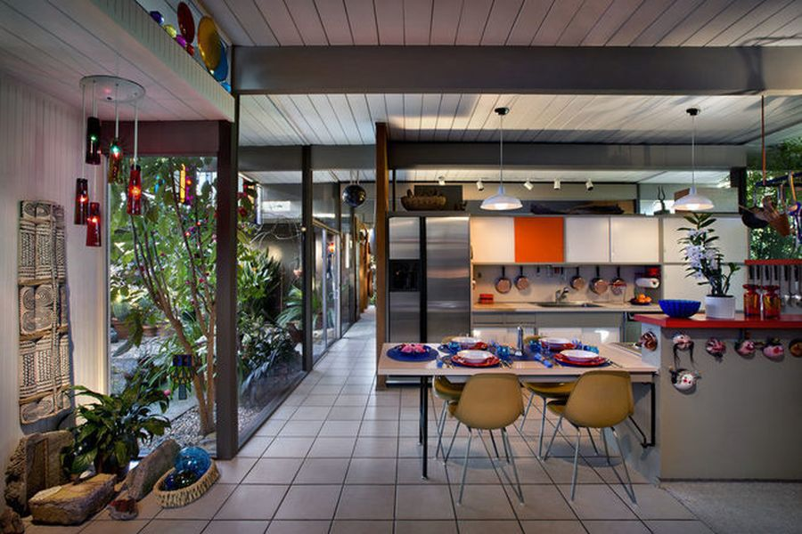 A midcentury modern kitchen with wood paneled walls and ceiling. The floor is tiled with linoleum. There is a table, chairs, and floor to ceiling windows looking out into a garden.