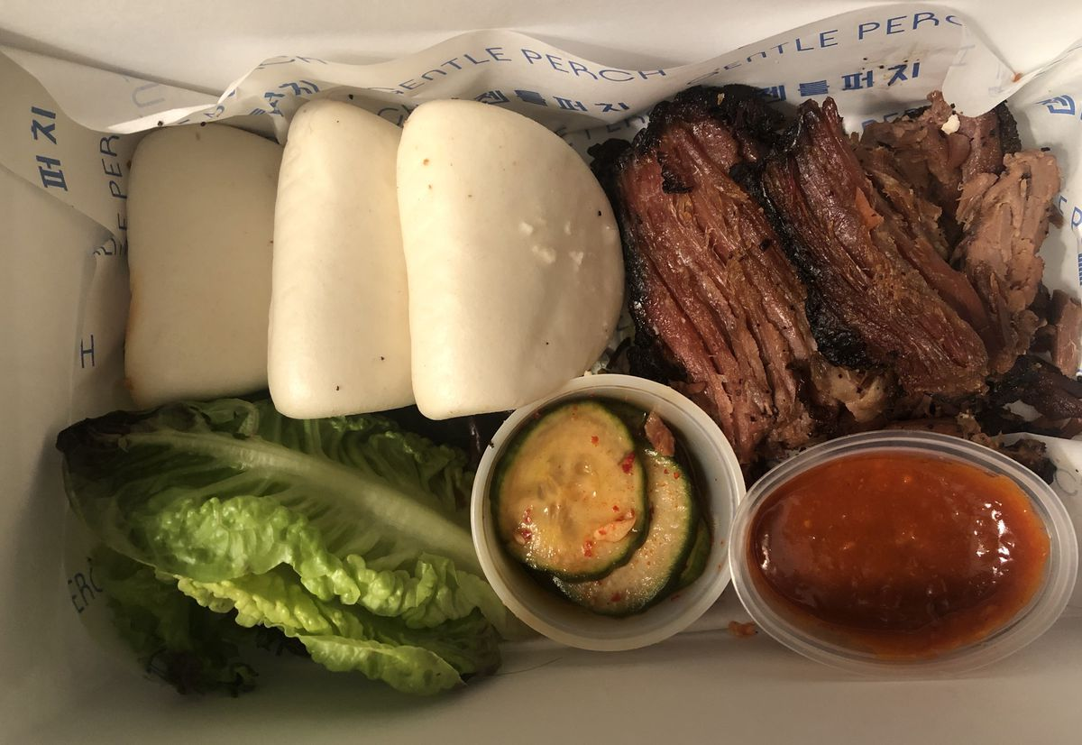 A white cardboard box filled with white bao buns, red meat, green lettuce, a cup of green pickles, and a small oval container of red sauce