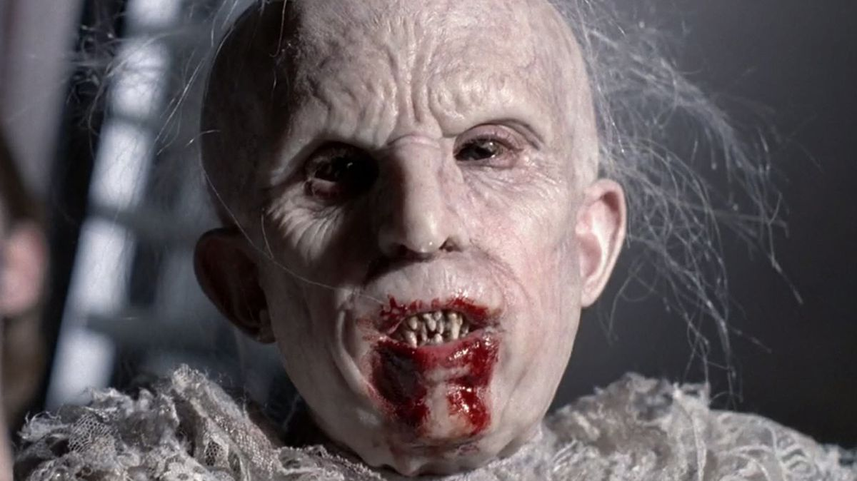 a pale child with a wrinkled face and sharp blood-splattered teeth