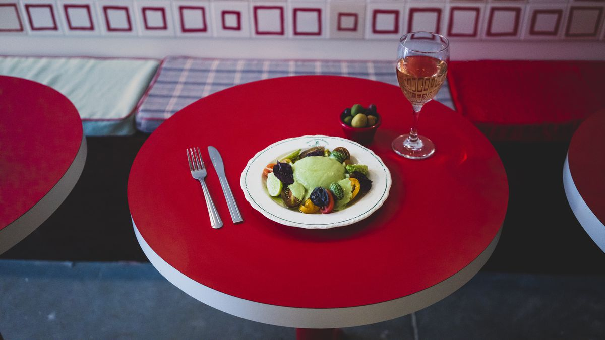 A plate of burrata, pesto, and vegetables sits in the middle of a red table with a glass of wine and a side dish filled with olives
