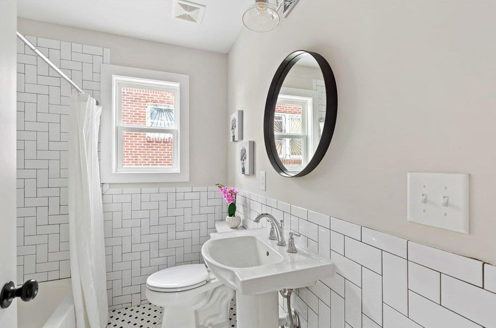 A white bathroom with a window and round mirror.