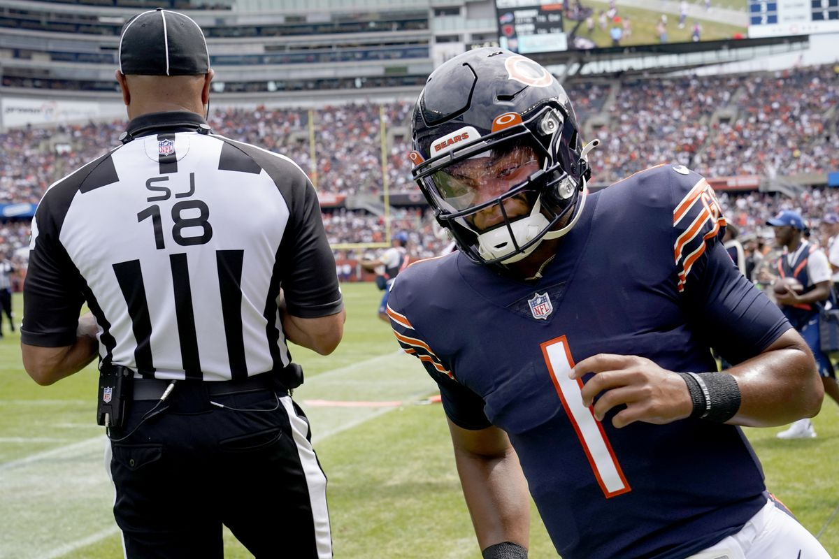 Chicago Bears quarterback Justin Fields (1) returns to the field behind line judge Byron Boston after picking up a first down during the second half of an NFL preseason football game against the Buffalo Bills Saturday, Aug. 21, 2021, in Chicago. (AP Photo/Nam Y. Huh) ORG XMIT: CXB