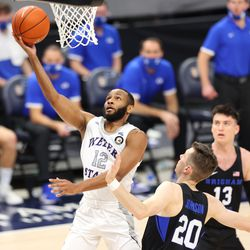 Weber State Wildcats guard Isiah Brown (12) goes up for a layup over Brigham Young Cougars guard Spencer Johnson (20) as BYU and Weber State play an NCAA basketball game at Vivint Smart Home Arena in Salt Lake City on Wednesday, Dec. 23, 2020.