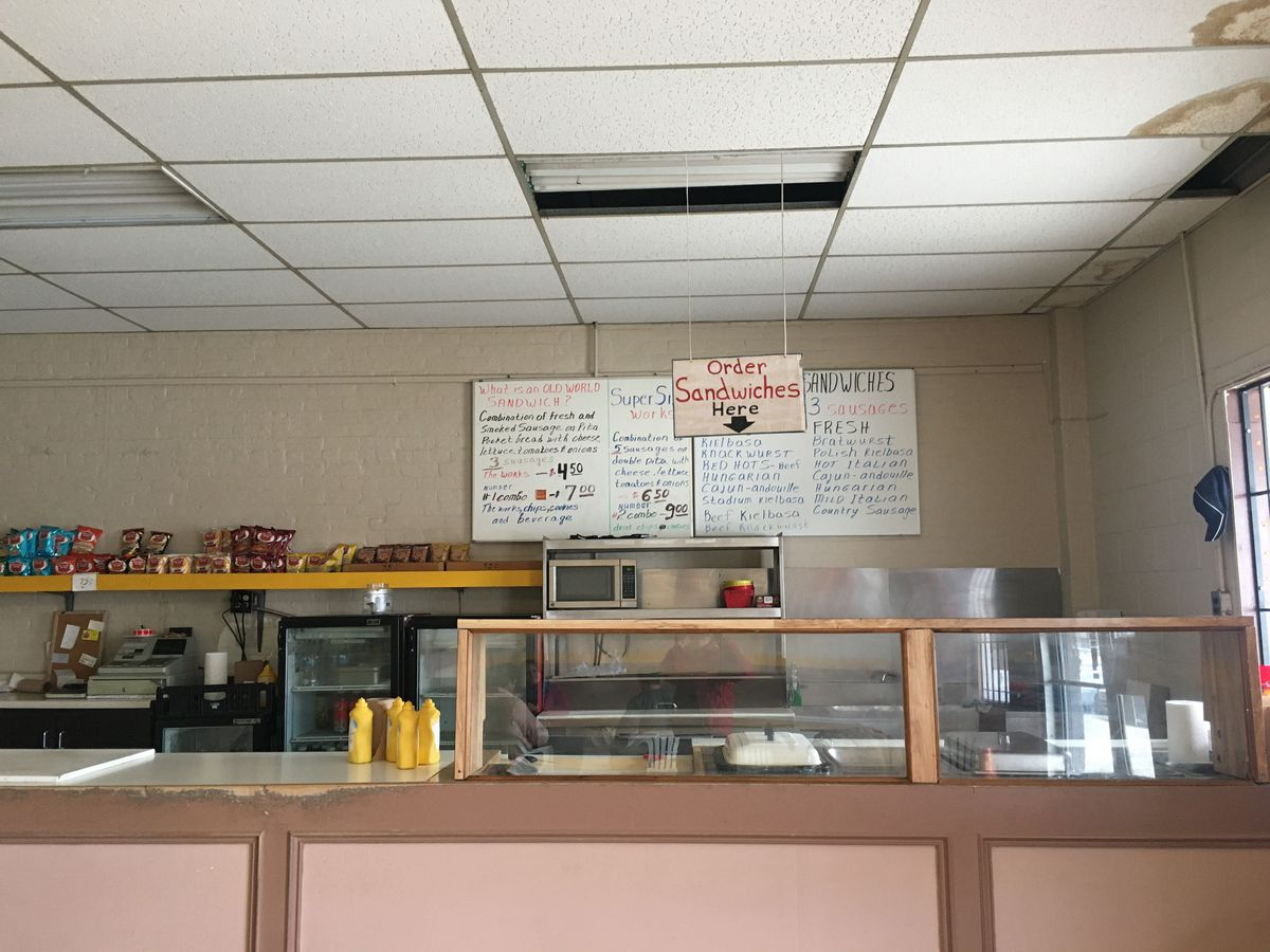 """A hand-written menu hangs on the wall behind a counter with a pink front, sneeze guards and a sign with an arrow reading """"Order Sandwiches Here."""""""