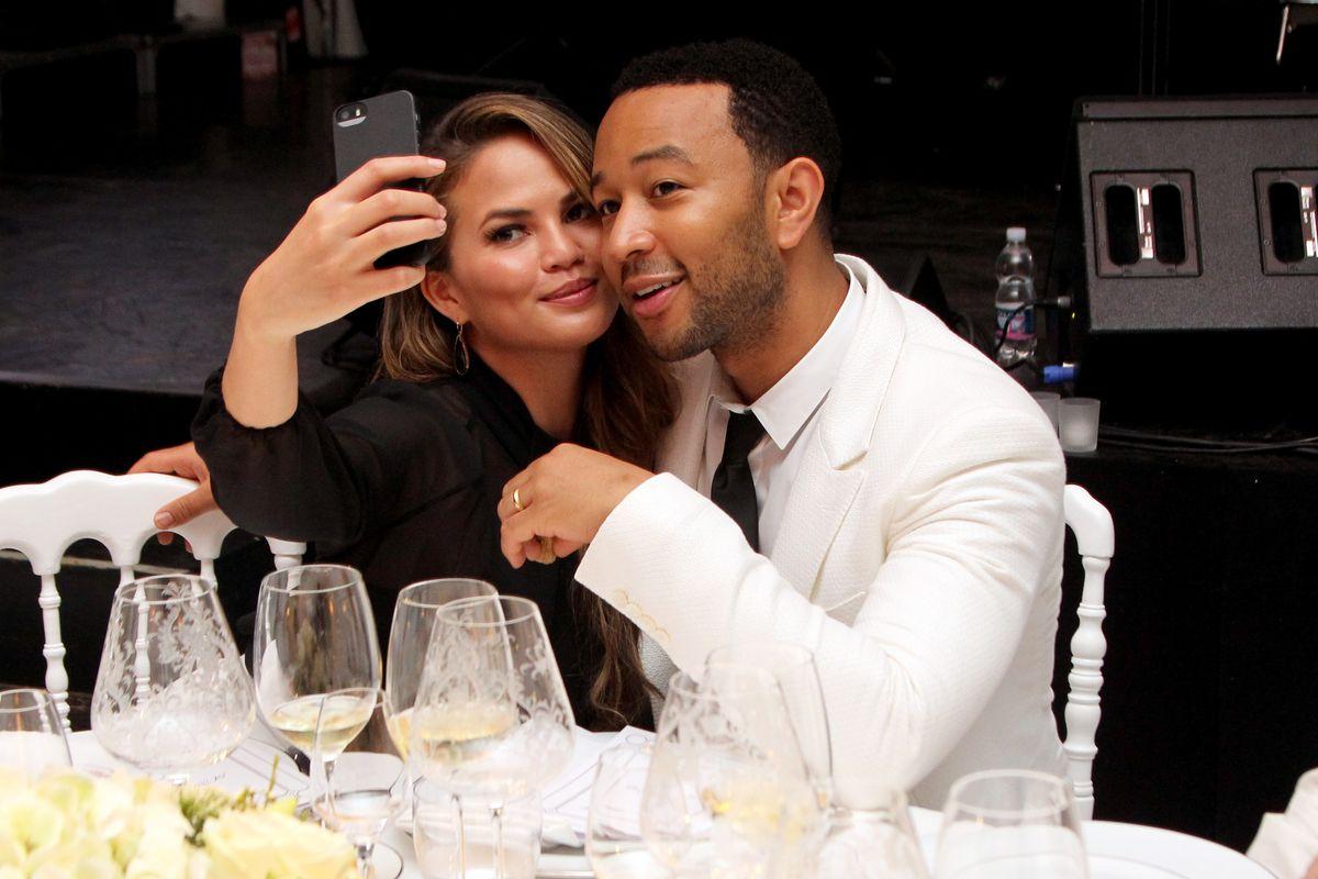Chrissy Teigen and John Legend take a selfie at a fancy benefit dinner