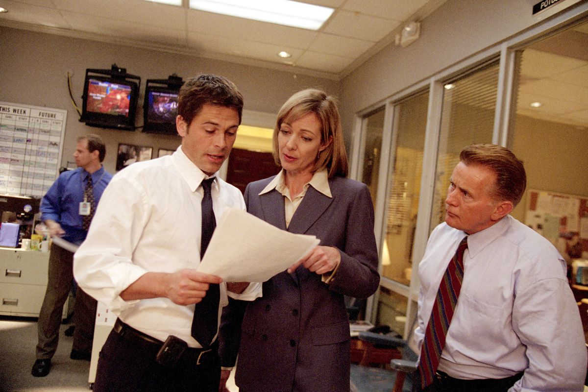 the cast of the west wing looking at some interesting documents