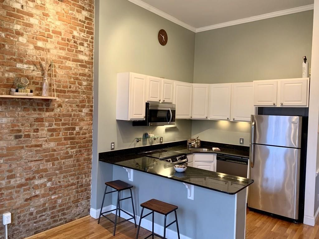 A small kitchen with a counter separating it from the living room of a condo.
