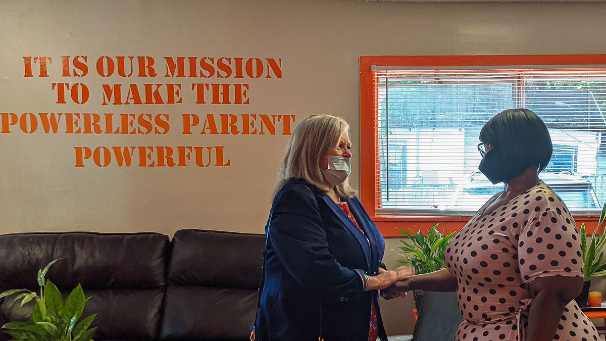 """Debra Moody shakes hands with Teresena Medlock at the Memphis Lift headquarters. Painted on the wall behind them is a statement that says, """"It is our mission to make the powerless parents powerful."""""""