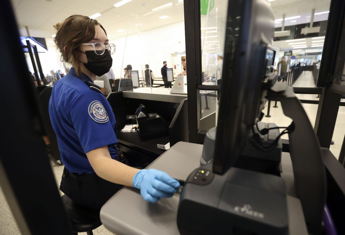 Staci Merten, a transportation security officer with the Transportation Security Administration, checks a passenger's identification at the TSA security checkpoint at Salt Lake City International Airport in Salt Lake City on Tuesday, May 18, 2021. Air travel is expected to increase this summer.
