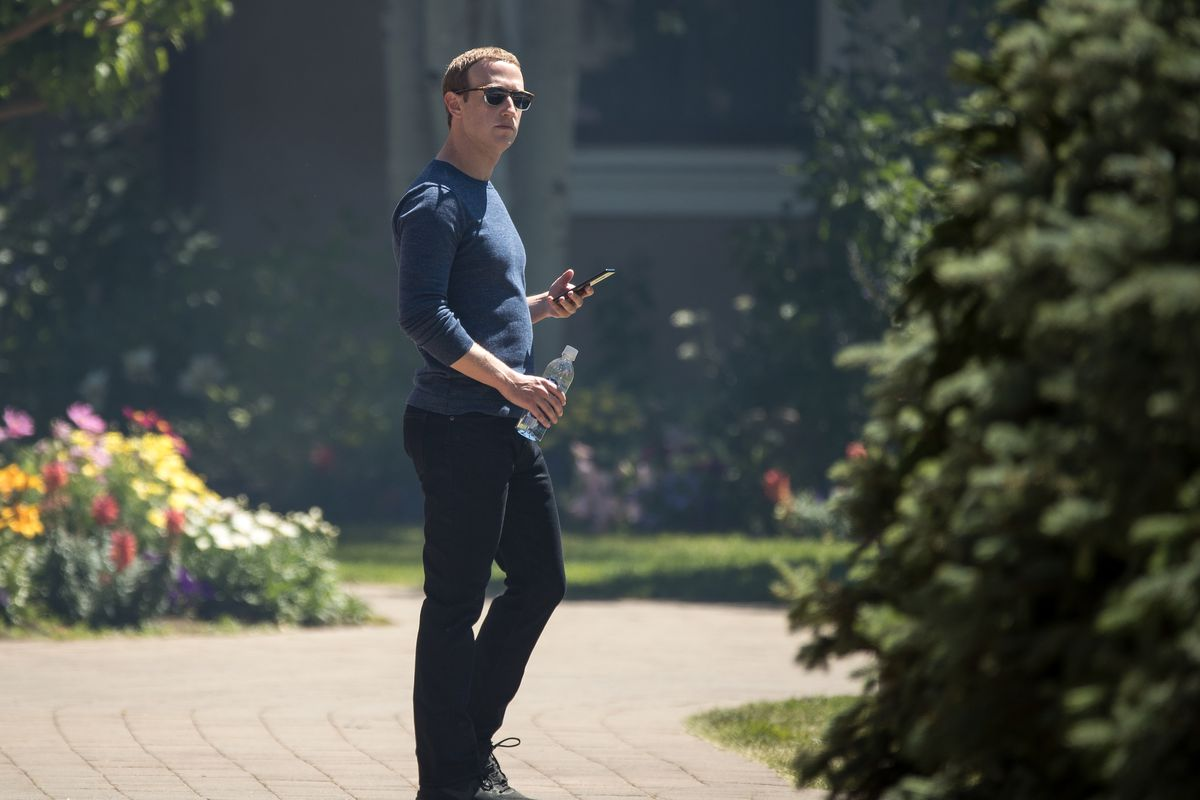 Mark Zuckerberg holding his phone and standing outside.