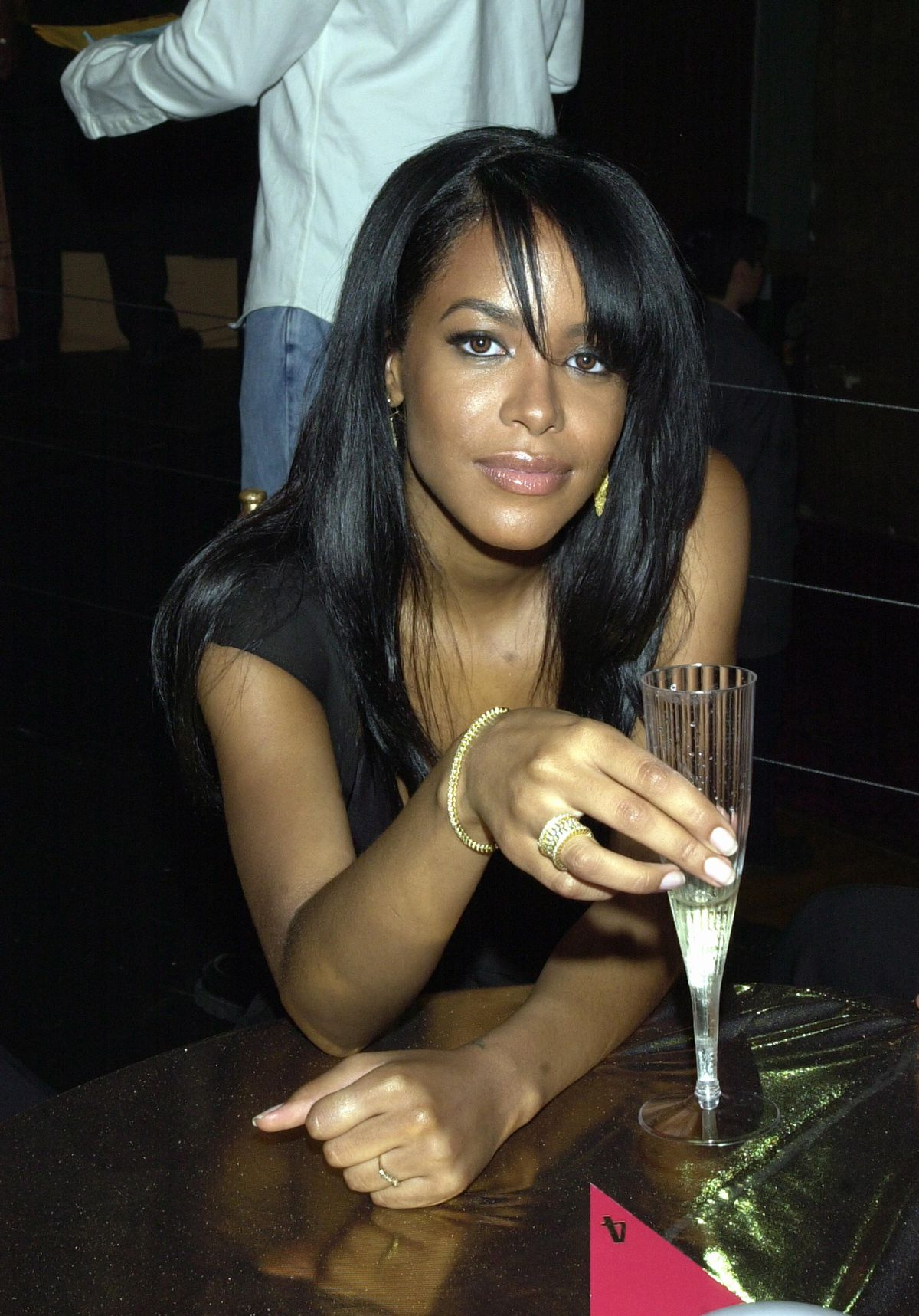 Aaliyah sitting at a table holding a champagne flute.