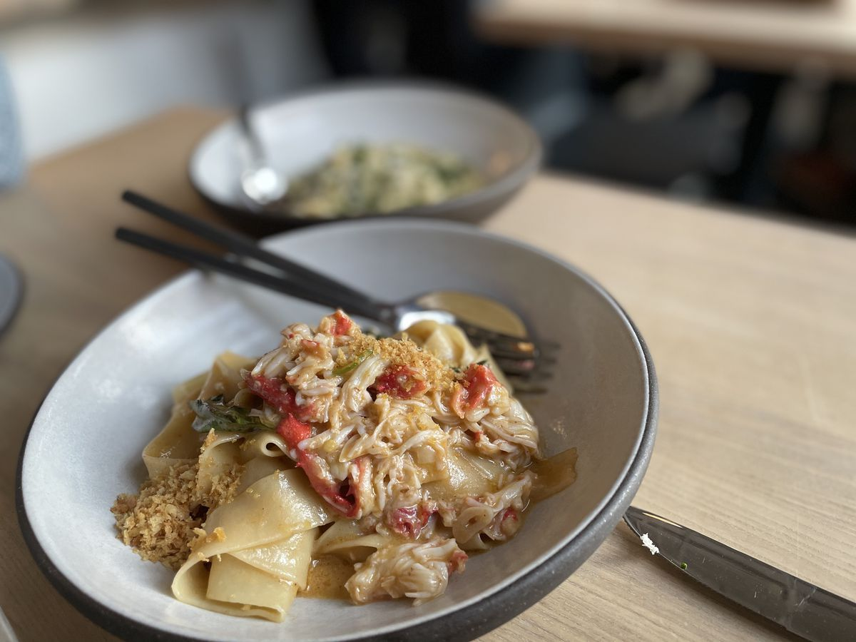 A bowl of fettuchini noodles covered in an earthy sauce and piled with shredded crab meat