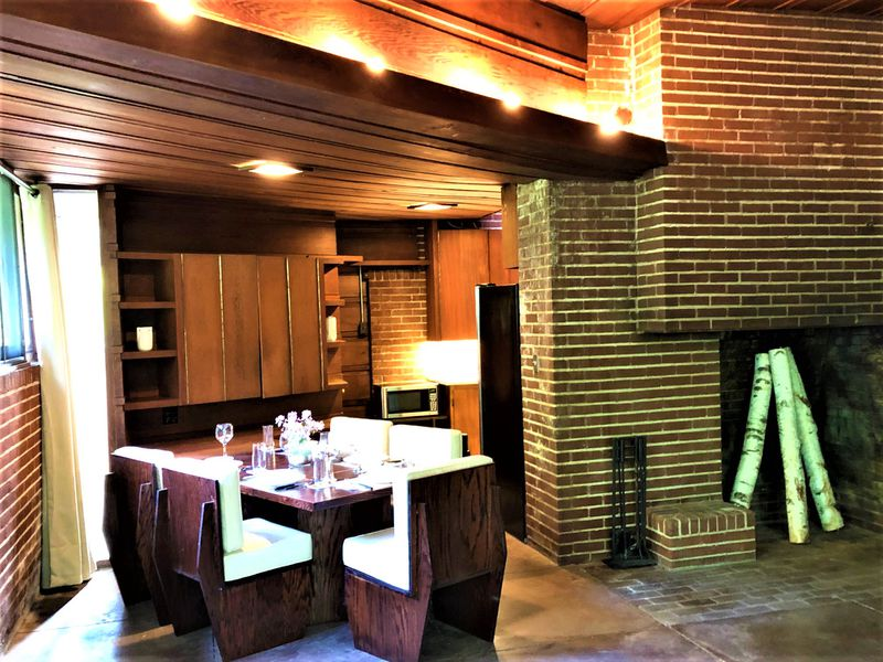 A dining room table with six chairs and cushions sits next to the brick fireplace.