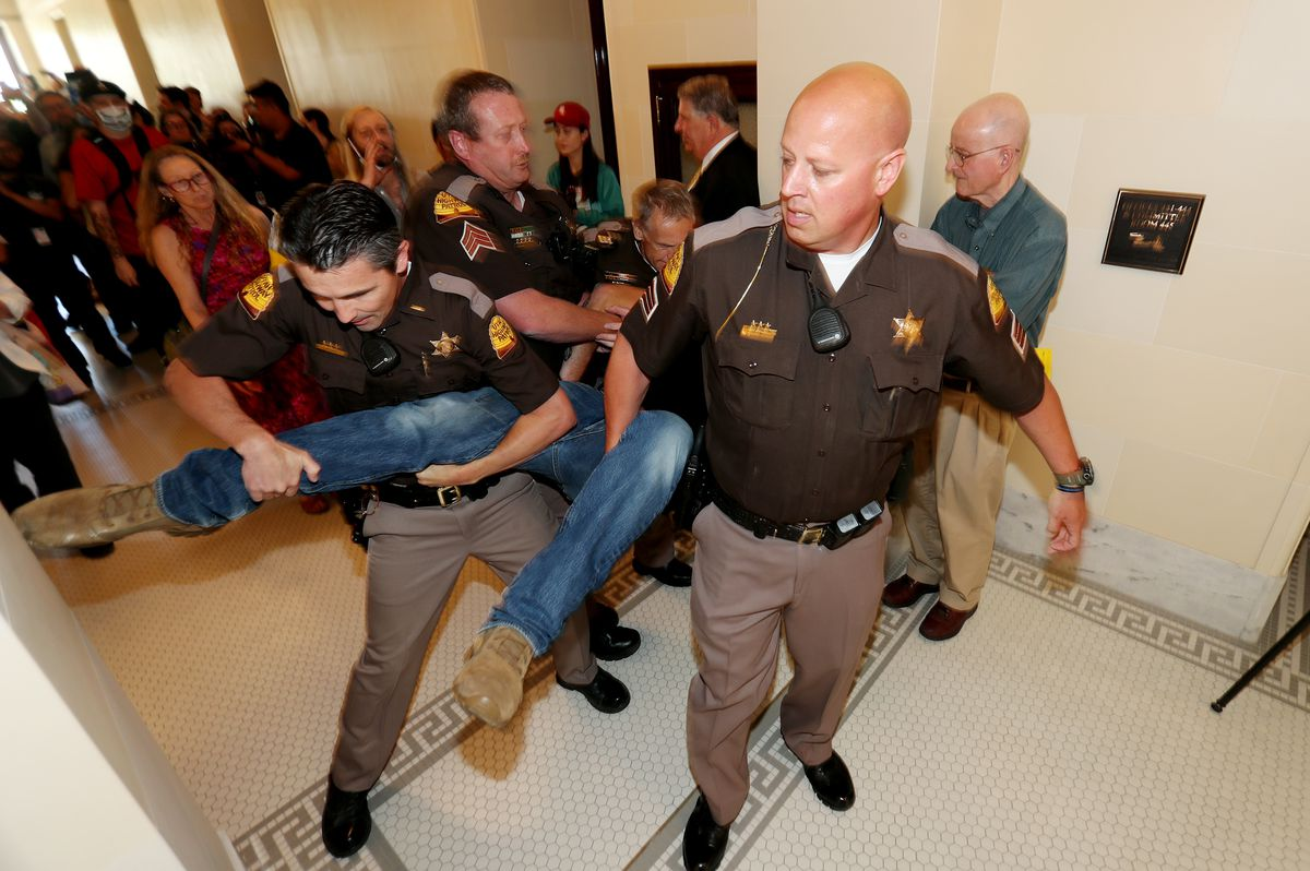 Utah Highway Patrol troopers remove a protester after he and several others disrupted a Utah Inland Port Authority board meeting at the Capitol in Salt Lake City on Wednesday, June 5, 2019.