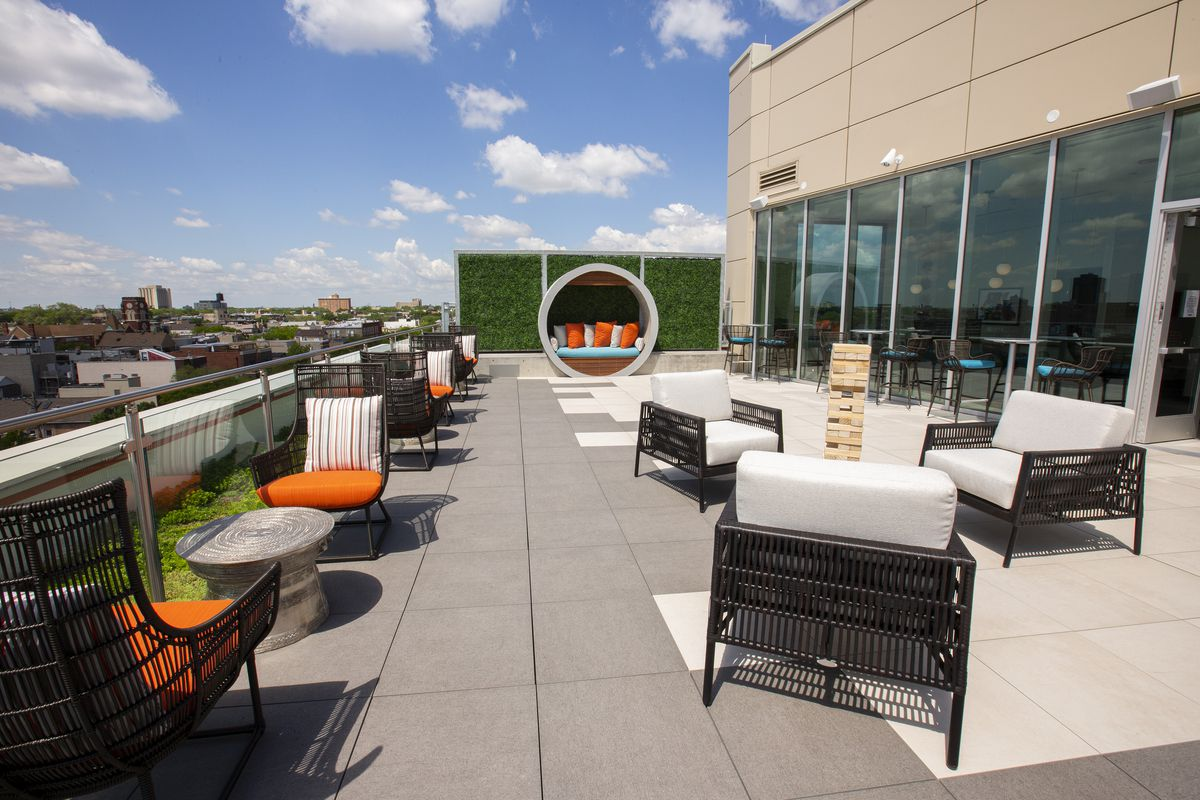 A rooftop bar with giant Jenga and seats.