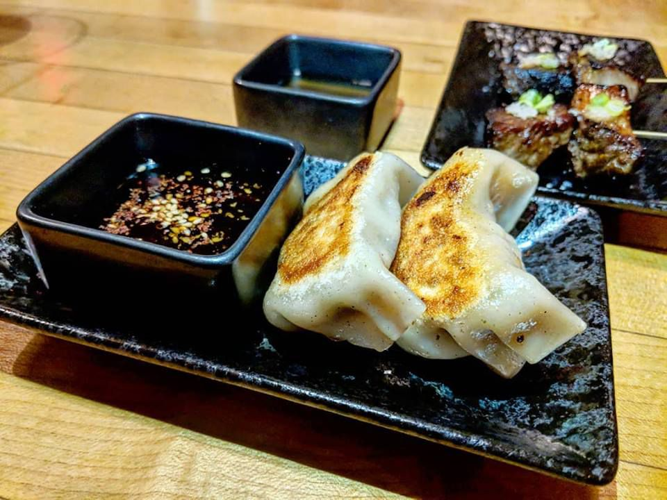 A couple of plump dumplings and a soy dipping sauce sit on a black plate at Momi Nonmi