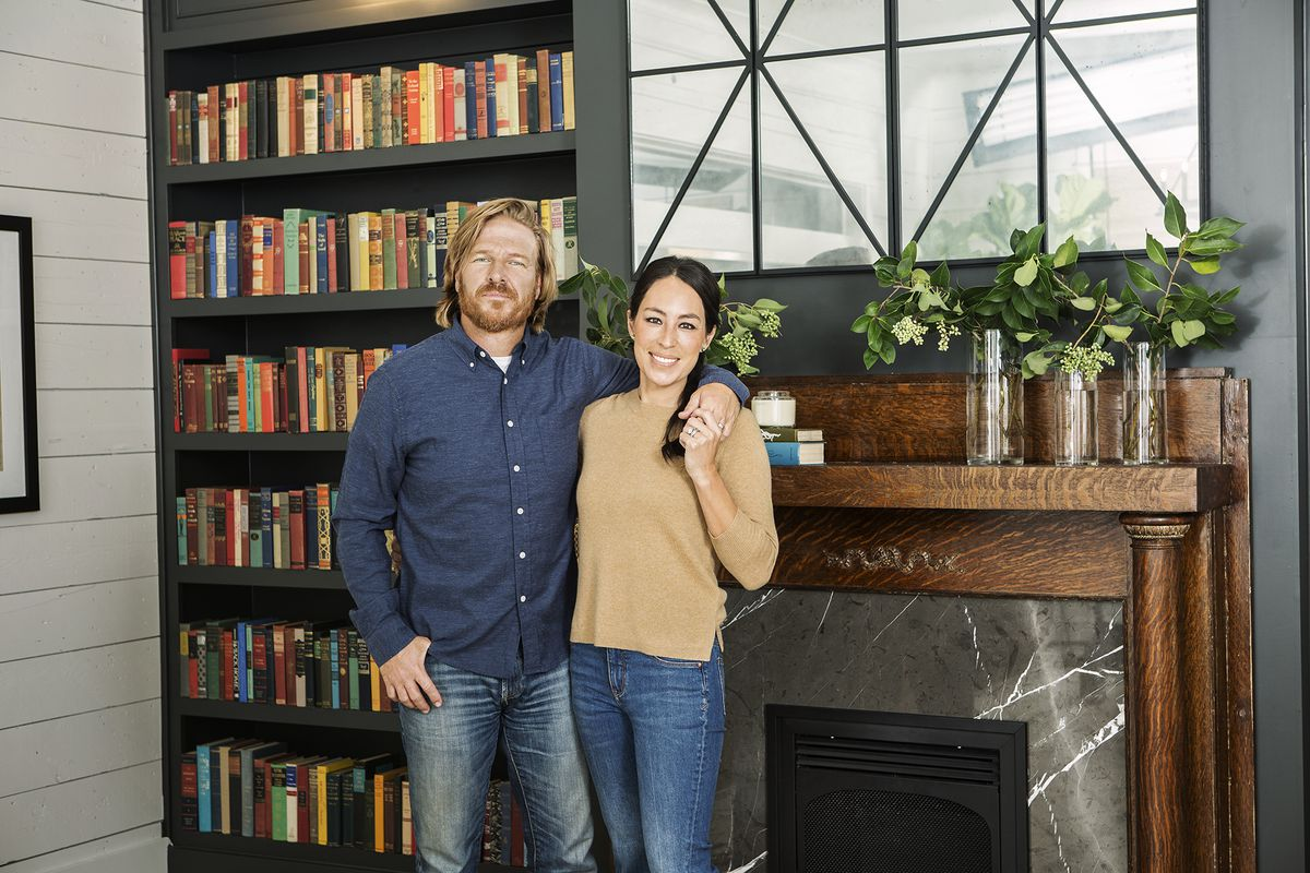 Television stars Chip and Joanna Gaines stand in front of a bookshelf, fireplace, and mantle.