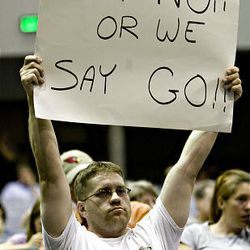 Ben Wallis of Riverton uses a sign to urge the Jordan School Board not to increase taxes during a meeting at Riverton High Tuesday. The board approved a 20 percent hike.
