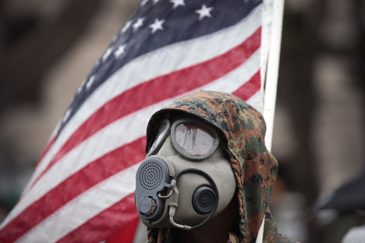 A person's head in a gas mask and camouflage hood in front of an American flag.