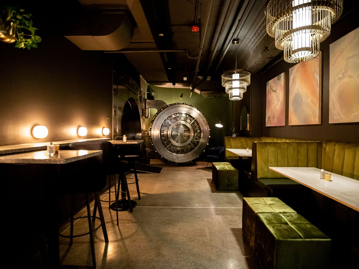 A dark restaurant dining room with a few booths on the right, tables on the left, and a bank vault at the back.
