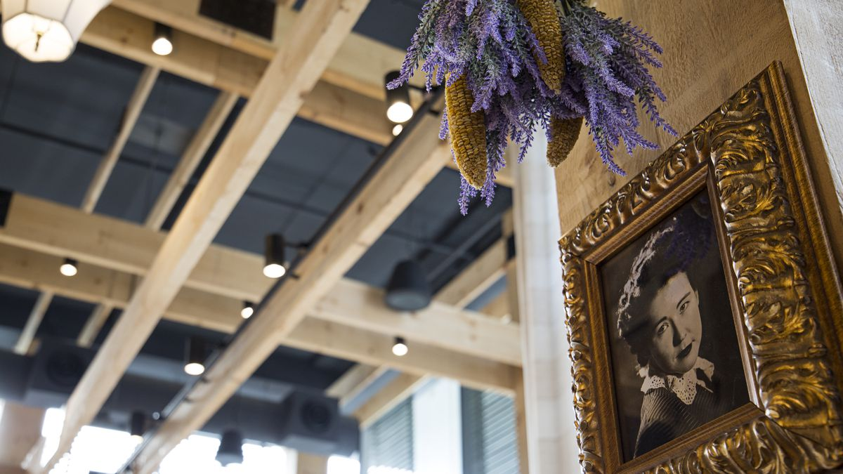 A detail shot of the Southern Proper interior, featuring a hanging purple plant and a framed old photograph