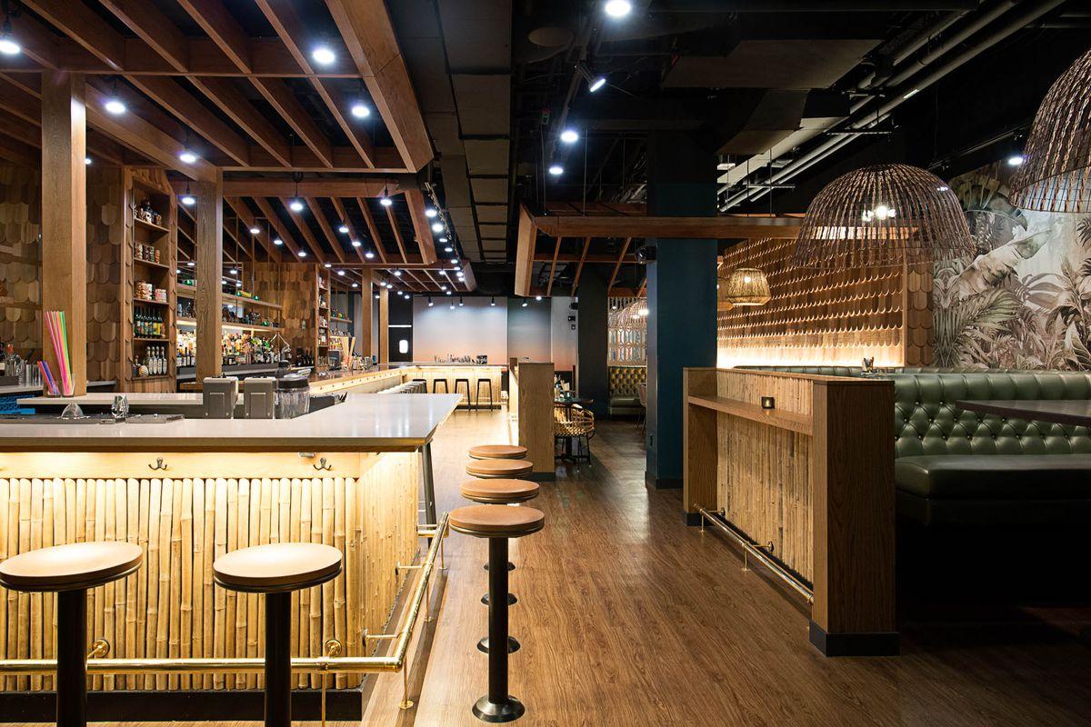 A dark, modern bar interior with a tiki theme