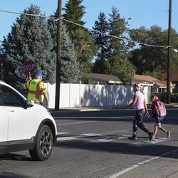 Newell Evans, left, mans a crosswalk as a woman and two children cross 1300 East near Millcreek Elementary School in Millcreek on Monday, Aug. 19, 2019.