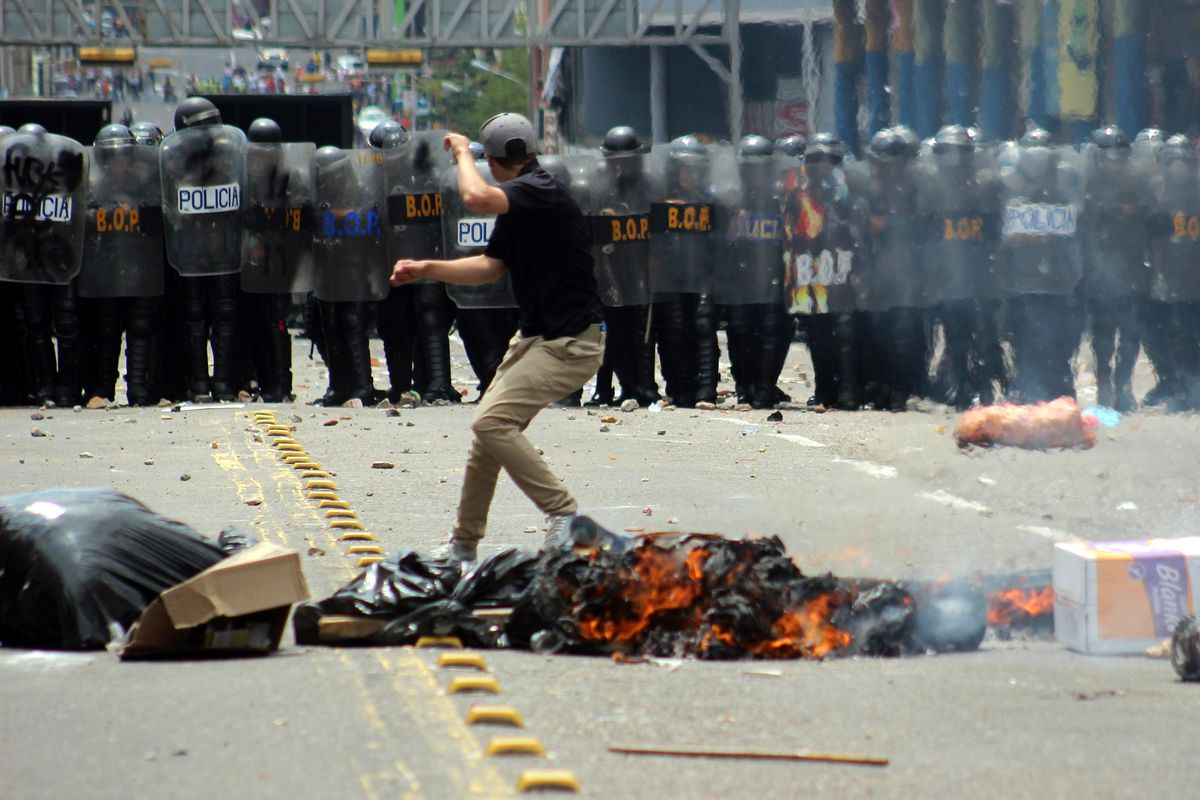 A student demonstrates in front of a line of riot police during a protest against Venezuelan President Nicolás Maduro's government in San Cristobal, Venezuela, on February 12, 2015.