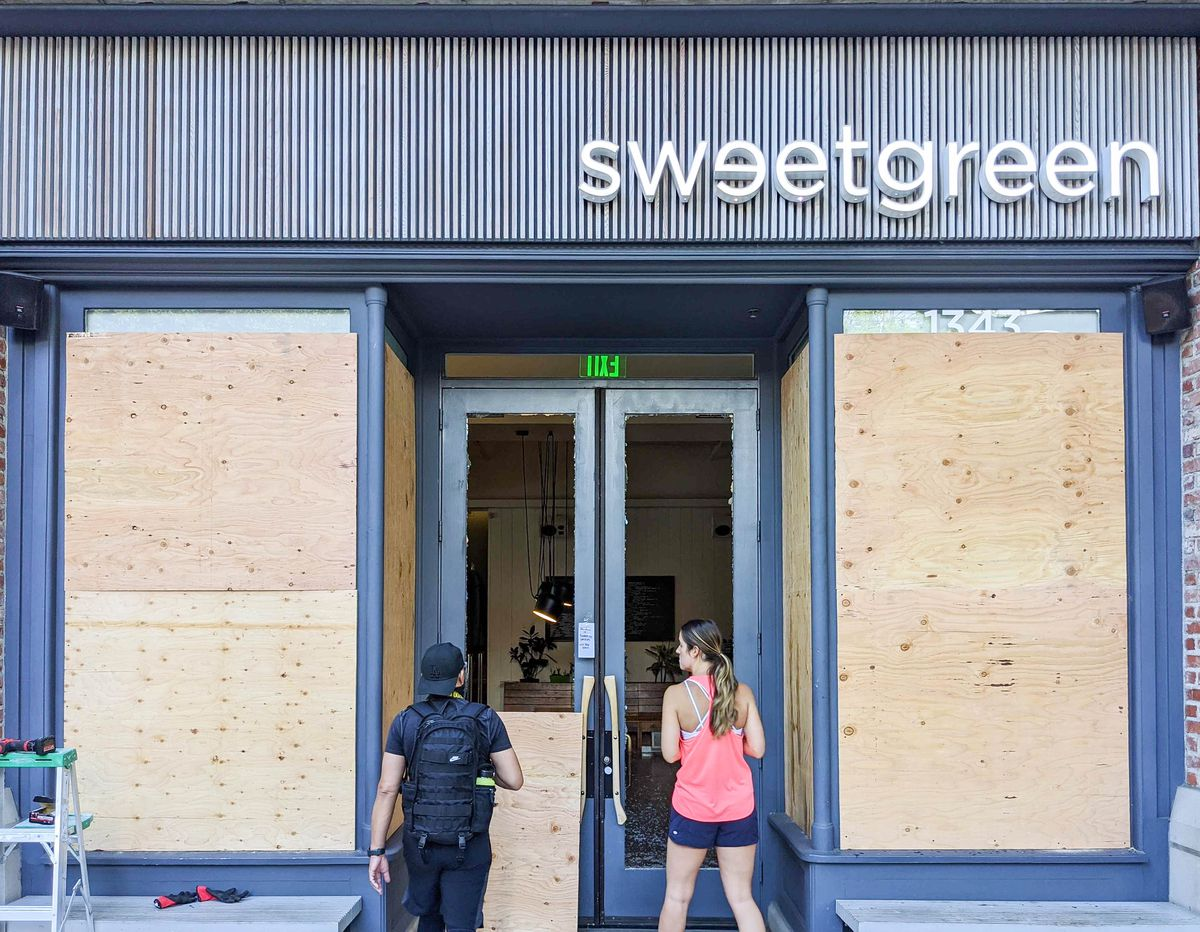 Two people look inside of a broken Sweetgreen as boards go up over the windows.