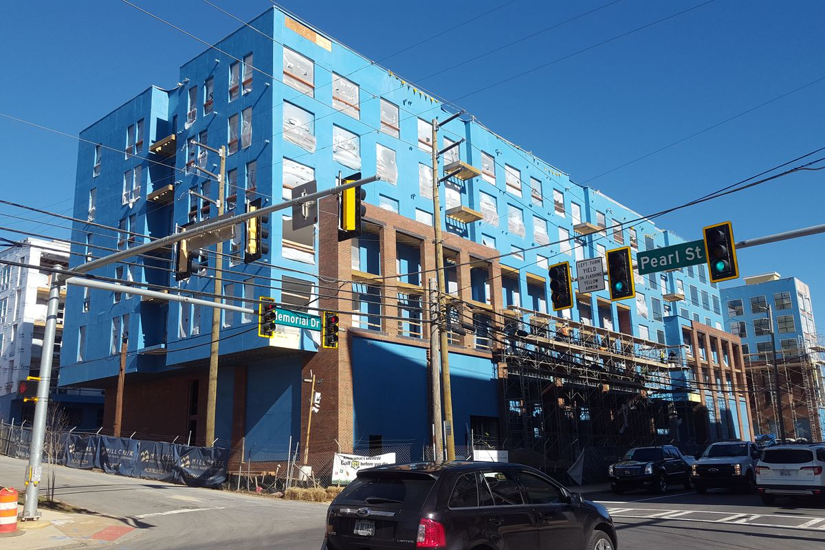 A building coated in bright blue construction wrapping.