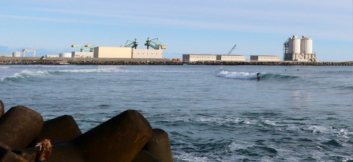 A photo from Kitaizumi Beach focused on a man in the distance surfing a wave. In the background are industrial buildings.