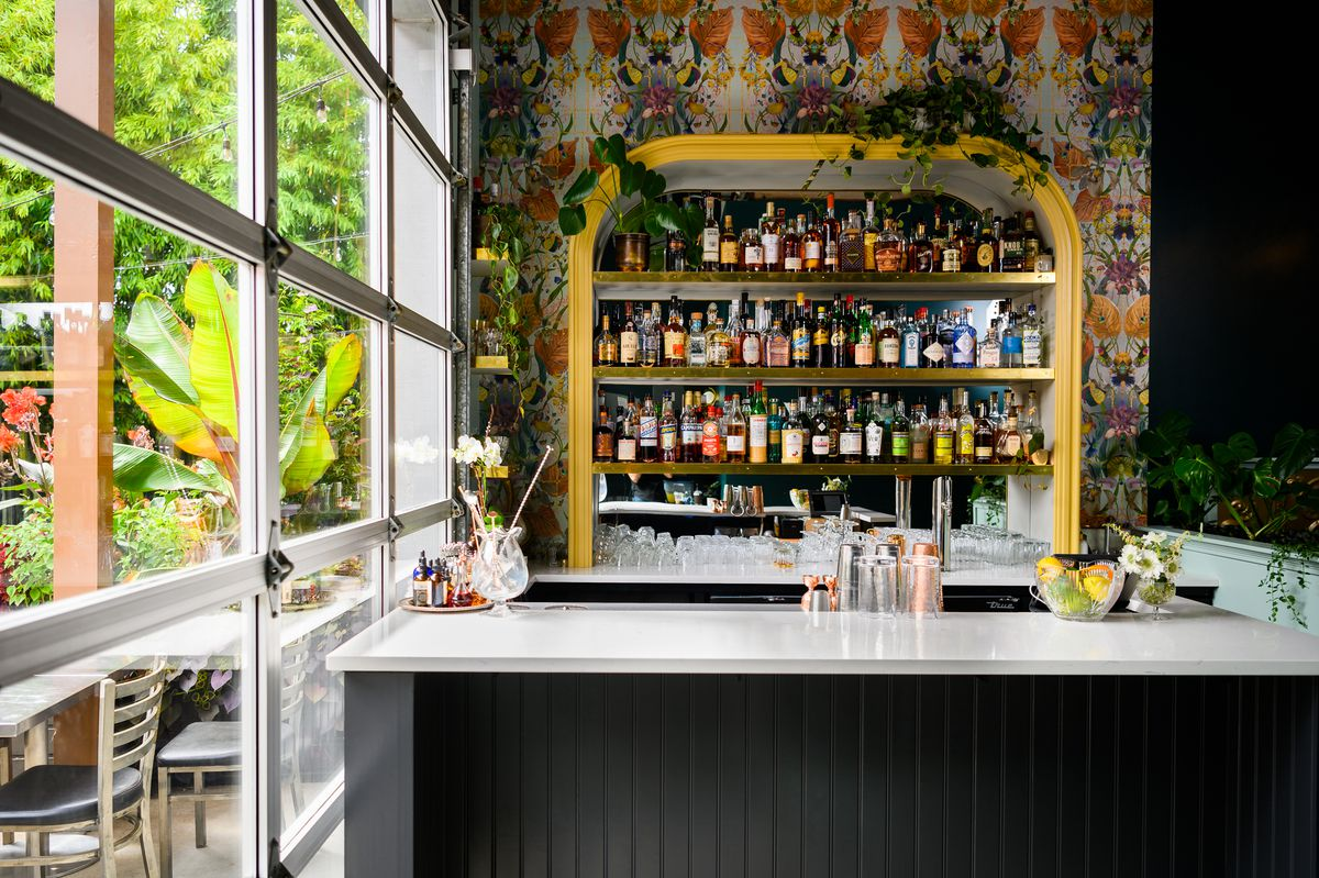 A white bar with a colorful backbar adorned with plants