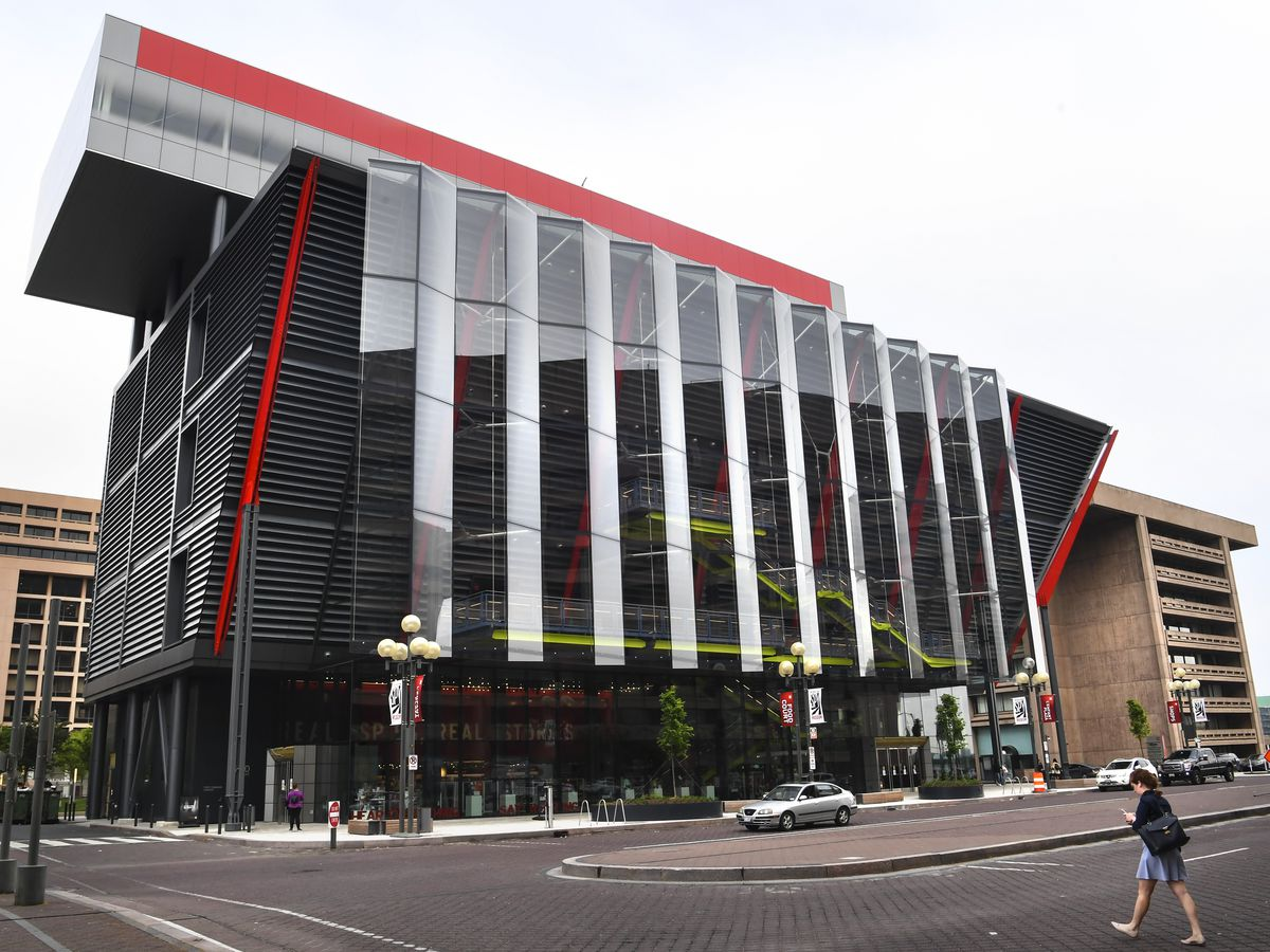 The exterior of the International Spy Museum in Washington D.C. The building is black with a glass exterior and sloped roof.