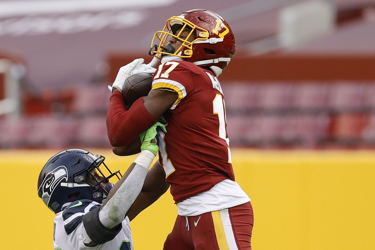 Terry McLaurin #17 of the Washington Football Team makes a reception over Ugo Amadi #28 of the Seattle Seahawks at FedExField on December 20, 2020 in Landover, Maryland.