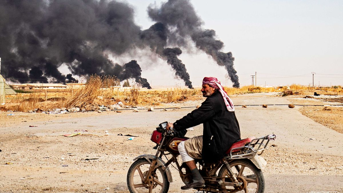 A man rides a motorcycle along a road with plumes of black smoke in the background.
