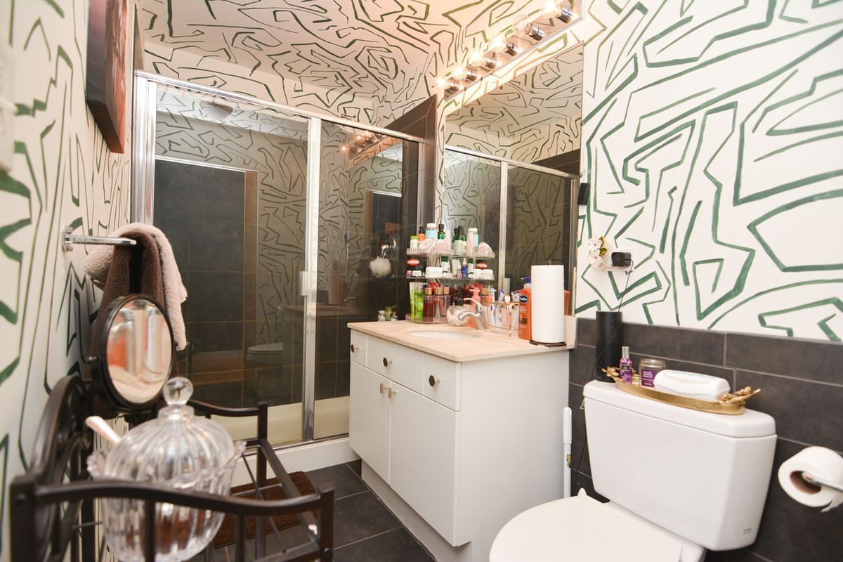 A bathroom with white and green striped walls. There is a glass walk-in shower.